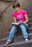 Girl with book on the stairs Stock Image