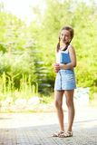 Girl with a book stands Royalty Free Stock Image