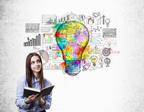 Girl with book and startup sketch with light bulb Stock Images