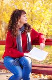 Girl with book in sunny autumn park Royalty Free Stock Photos