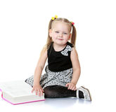 Girl with a book in their hands. Beautiful little girl with long blonde bunches that adhere colorful erasers. Girl sitting on the floor or turn the pages of stock images
