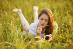 Girl with a book of wildflowers Stock Photos