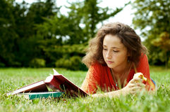 The girl with books. Lying on a grass Stock Photo