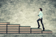 Girl and books. The girl rises upwards on a ladder from books Royalty Free Stock Images