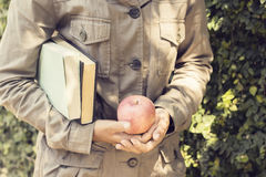 GIrl with books and a apple. Close up Royalty Free Stock Image