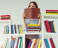 Girl with books. Beautiful young girl in casual clothes is hiding behind the book and looking away while standing among bookcases Stock Images