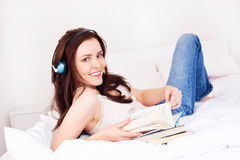 Girl with books and earphones Royalty Free Stock Photos