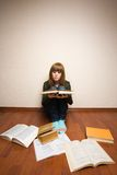 Girl with books on the floor Royalty Free Stock Images