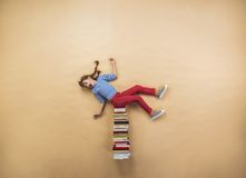 Girl with books. Happy girl is playing with group of books in studio Stock Photo