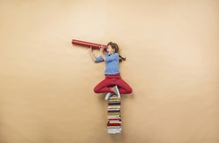 Girl with books. Happy girl is playing with group of books in studio Royalty Free Stock Photo
