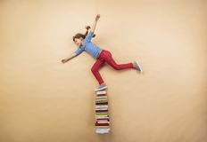 Girl with books. Happy girl is playing with group of books in studio Stock Photography
