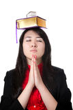 Girl with books on her head. Asian girl with books on her head and prayer gesture isolated on white background Royalty Free Stock Photo