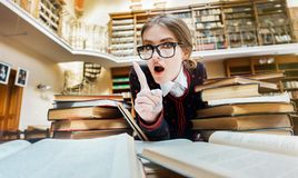 Girl with Books in the Library. Smart blonde girl wears glasses studying at the library table full of books royalty free stock photo