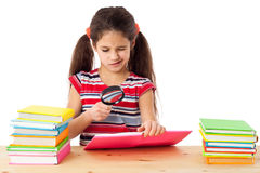 Girl with books and magnifier Stock Photography