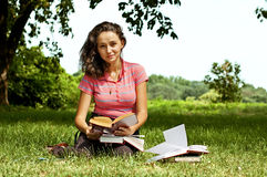 The girl with books sitting on a grass. The girl sitting on a grass, reading a book Royalty Free Stock Photo