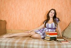 Girl with books on sofa Stock Photography
