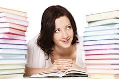 Girl between books stacks reading. Stock Photo