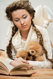 Girl with books and toy. Young girl reading book lying on the floor with toy Stock Image