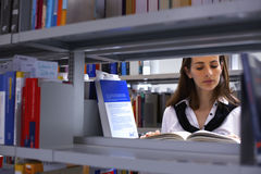 Girl between bookshelves reading Stock Images