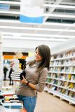Girl in bookstore choosing books stock images