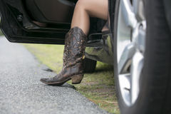 Girl in boots getting out of car. A beautiful woman wearing cowboy boots prepares to exit a car royalty free stock photos