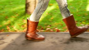 A girl in boots steps on the sidewalk against the background of green grass and autumn leaves stock footage