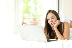 Girl bored browsing media in a laptop. Lying on a bed at home Stock Photo