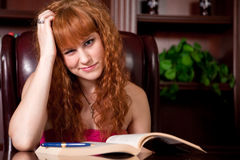 Girl Bored with Studying. Pretty girl making a bored face while reading a book Royalty Free Stock Image