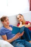 Girl boring while her boyfriend reading book Stock Photos