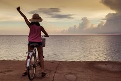 Girl both hand background sunset at the sea. Asia teenager girl sit on the bike with both hand cheerful background sunset at the sea with copy space stock photo