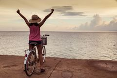 Girl both hand background sunset at the sea. Asia teenager girl sit on the bike with both hand cheerful background sunset at the sea with copy space royalty free stock images