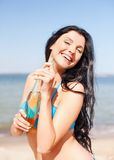 Girl with bottle of drink on the beach Royalty Free Stock Photos