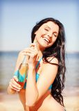 Girl with bottle of drink on the beach Stock Images