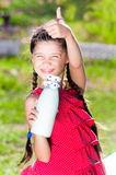 Girl with bottle of milk shows thumb up Stock Photos