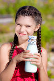 Girl with bottle of milk in summer Royalty Free Stock Photography