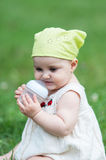 Girl with bottle sitting in a meadow Royalty Free Stock Photography