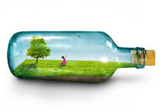Girl in bottle. A woman stuck inside a glass bottle flies a kite