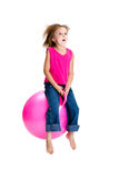 Girl bouncing. Young girl bouncing on a pink space hopper Stock Photography