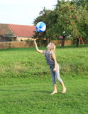 Girl bouncing inflating ball Stock Images