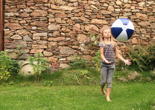 Girl bouncing inflating ball. Little girl - barefoot kid bouncing inflating ball with stone wall behind royalty free stock images