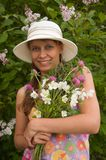 The girl with a bouquet. The girl at a blossoming bush of a lilac with a bouquet of wild colours stock images