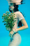 Girl with a bouquet. Girl under the water with a bouquet of roses Stock Photo
