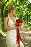 Girl with a bouquet. Of roses in green alley Royalty Free Stock Photos
