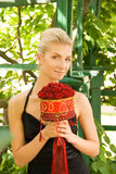 Girl with a bouquet. Beautiful blond girl with a bouquet of red roses Royalty Free Stock Photos