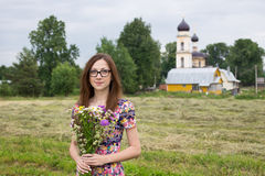 Girl with bouquet on background of village church Royalty Free Stock Photos