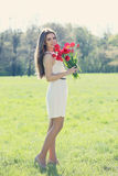 Girl with a bouquet. Beautiful long-haired romantic girl with a bouquet of tulips Stock Photography