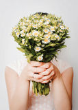 Girl with bouquet of camomile at white wall Royalty Free Stock Photos