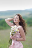 Girl with bouquet of chamomile on open air Stock Photos