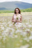 Girl with bouquet chamomile posing on meadow of chamomiles Stock Images