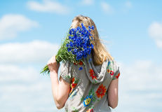 The girl with a bouquet of cornflowers on sky background. stock image
